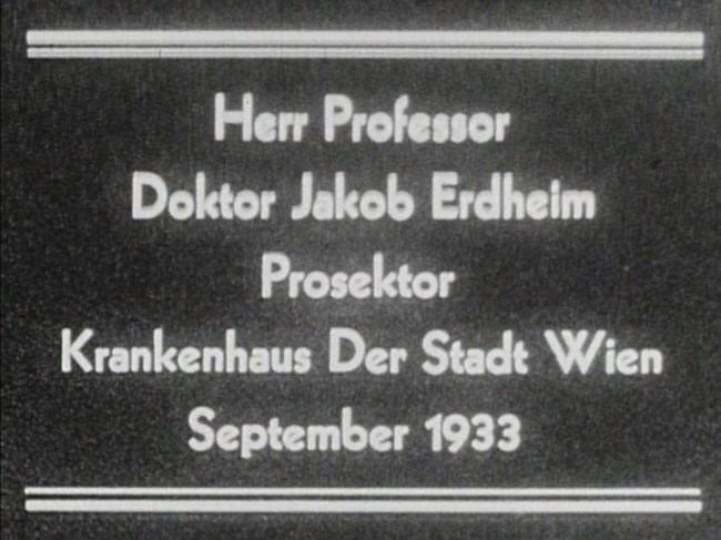 Grainy still from film that reads: Herr Professor Doktor Jakob Erdheim Prosektor Krankenhaus Der Stadt Wien September 1933