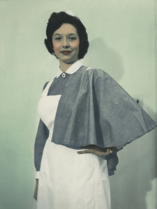 A woman in a white cap, grey shirt, white apron and grey half cape with a red cross brooch.