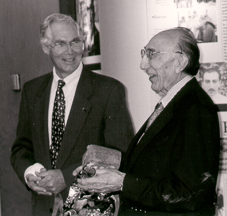Dr. Lindberg and Dr. Debakey stand together smiling, DeBakey hold a brick and wrapping paper.