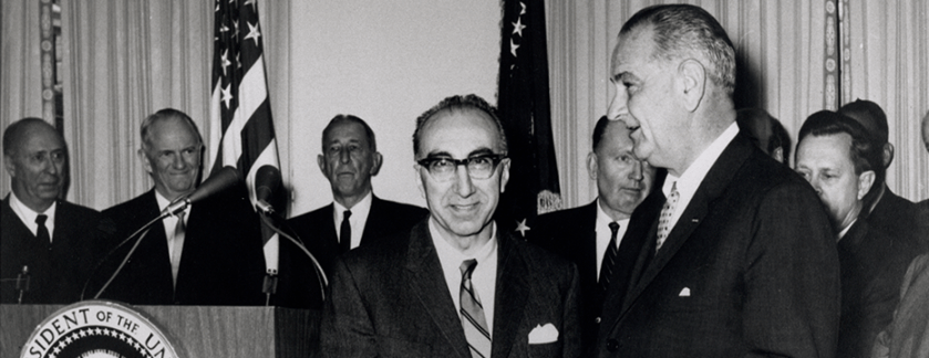 President Johnson takes papers from DeBakey as they stand beside a podium.