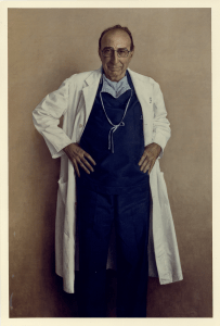 A full length portrait in scrubs and long white coat.