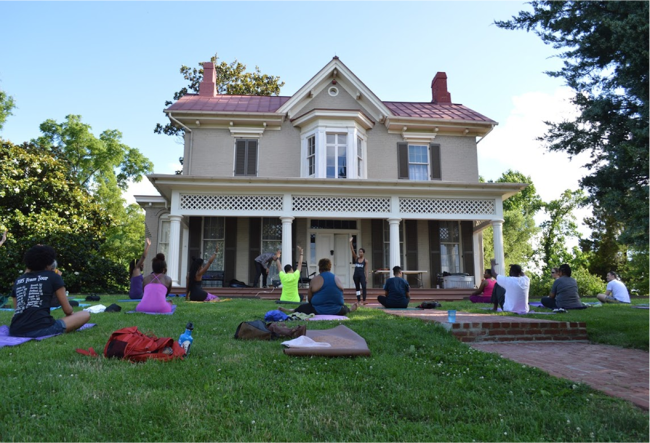 A group of people do yoga on the lawn in front of a large house.