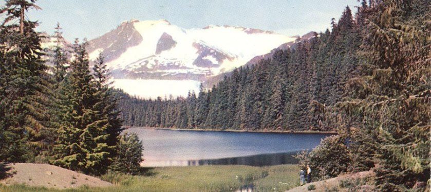 A color halftone printed postcard showing two small figures and a sweeping landscape of mountains, lakes and evergreen forest.