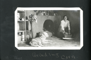 A woman in gingham kneels on the ground by an adobe fireplace grinding corn, a dog lays by the fireplace.