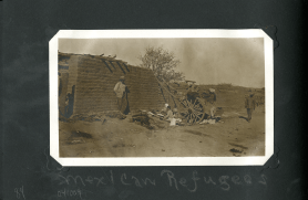 A family camped by a wall with a two wheeled cart and belongings strewn about.