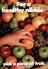 A hand is reaching for an orange in a pile of fruit that also includes apples, grapes, pears, and bananas