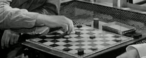 A hand moves checkers on a board.