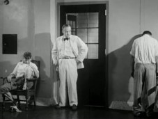 Joe stands by the door of a room where two men sit and stand in attitudes of distress.