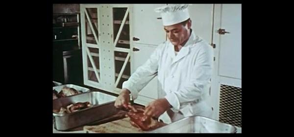 A chef prepares a chicken on a cutting board.