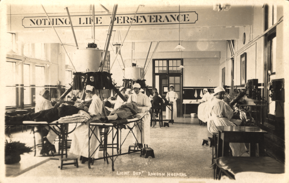 Postcard featuring a black and white photograph of nurses treating patients with tuberculosis of the skin with Finsen's Therapy at the London Hospital.