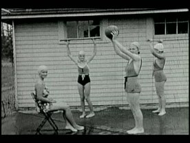 A screen shot of four girls in swimsuits exercising outdoors.