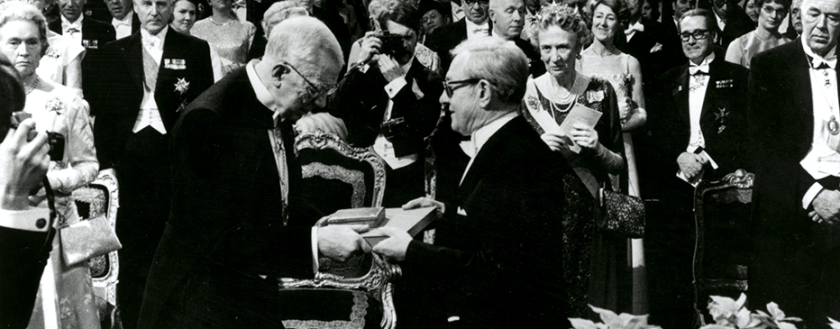 A man receives an award before a room full of people in formal dress.