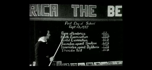 A teacher reviews a classroom's vaccination status on a blackboard.