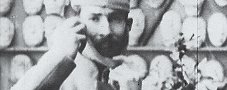 A bearded man holds a mask by his face.