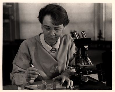 A woman working at a microscope.