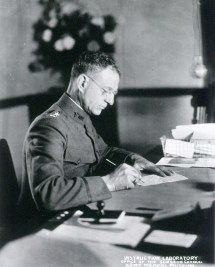 Photograph of man in uniform sitting at desk.