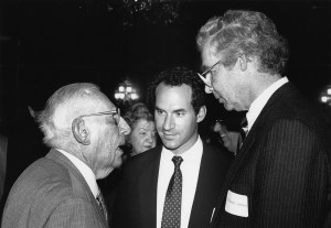 Three men in suits stand together at an event.