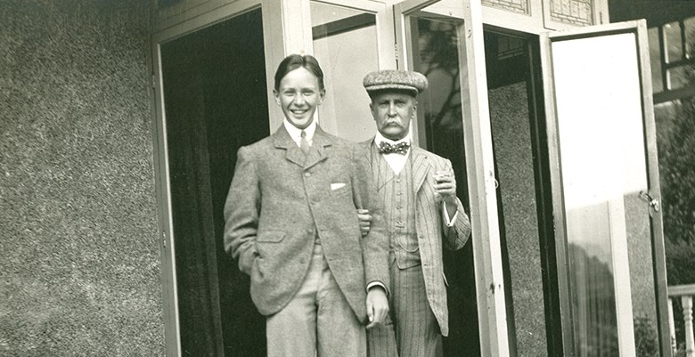 An older man and a teenage boy post together on a porch.