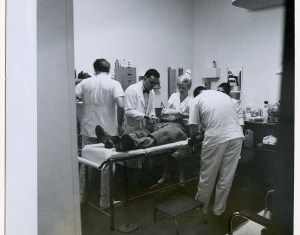 A patient lays on a narrow metal cot in a room crowded with medical personnel.