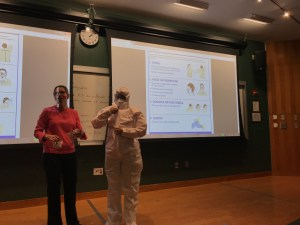People demonstrate how to put on protective clothing during a presentation.