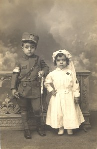Postcard featuring a black and white photograph of children posing as a soldier and a Red Cross nurse.