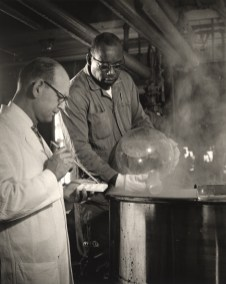 Laboratory Technician wearing a white lab coat works with another employee, pouring a substance into a pot