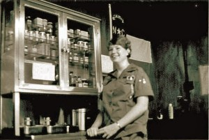 A woman in uniform by a cabinet of medical supplies.