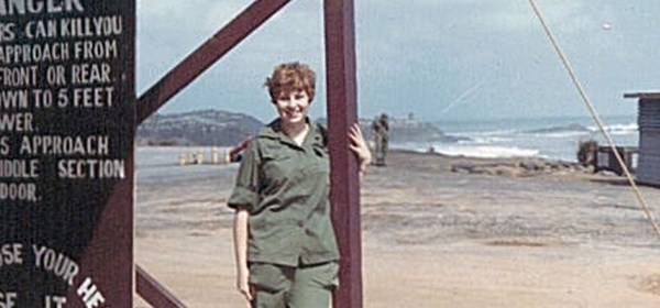 A young woman in uniform stands by a sign in front of a helicopter pad.
