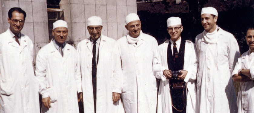 Seven men in white coats and surgical caps pose outdoors for a photograph.