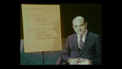 A man seated next to a poster with outline headings Rapport, Appraisal, Theraputic Responses.