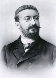 A formal vignette portrait of a man in a suit with glasses and short beard and mustache.