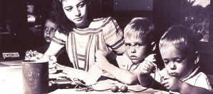 Three young children work with large beads and string while a young woman watches.