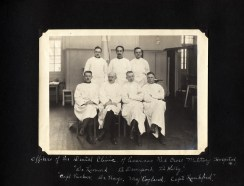 Seven men in operating cloghes pose for a portrait.