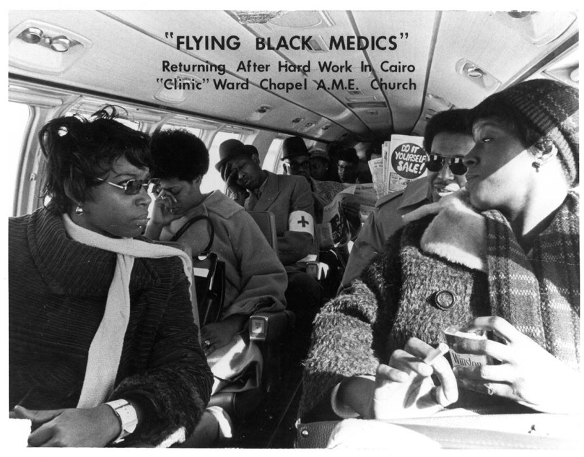 African American women and men sit in a small plane
