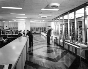 Black and white photograph of men standing in library entrance.