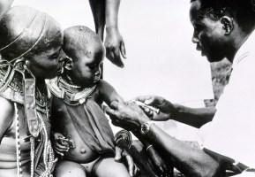 A black man gives an injection to an African child with a syringe.
