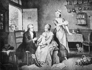 A man uses a lancet to vaccinate a baby on a woman's lap in a rustic room, a cow looks in the window.
