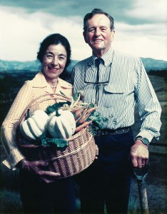 A man and woman stand outdoors, she holds a basket of produce and he holds a shovel.