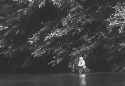 A woman rides a horse, shoulder deep in a river.