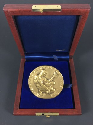 A golden medal featuring a naked man holding a crystal, in a presentation box.