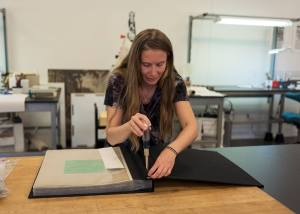 A woman uses a screw driver to loosen the binding on a large album.