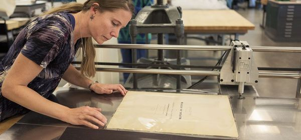 A conservator leans over and aligns a page in a plastic cover on a machine that will seal it.