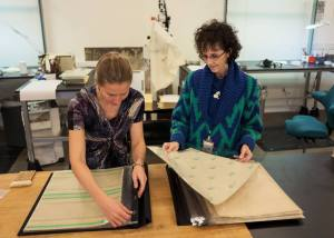 Two women work together putting plastic covered pages in a large album.