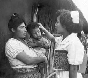 A woman in a nursing uniform carrying a notebook touches the head of a child in a woman's arms.