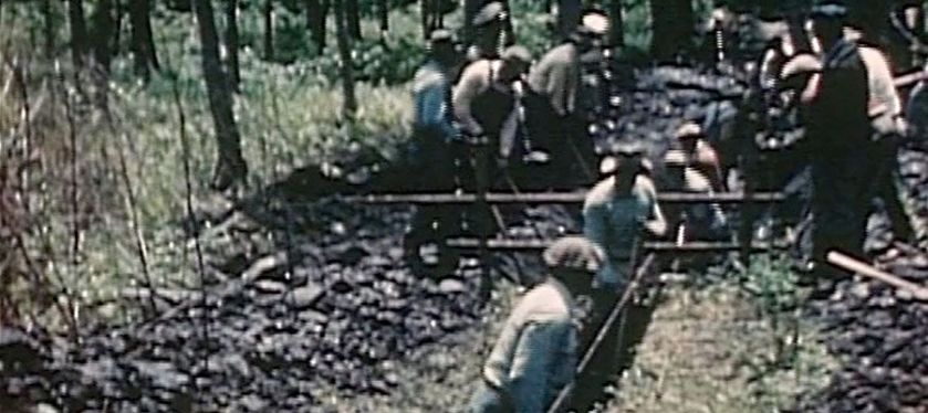Men digging a ditch marked with string.