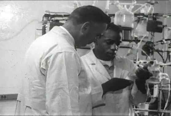 A black man in a lab coat shows a sample to a white man in a lab coat.
