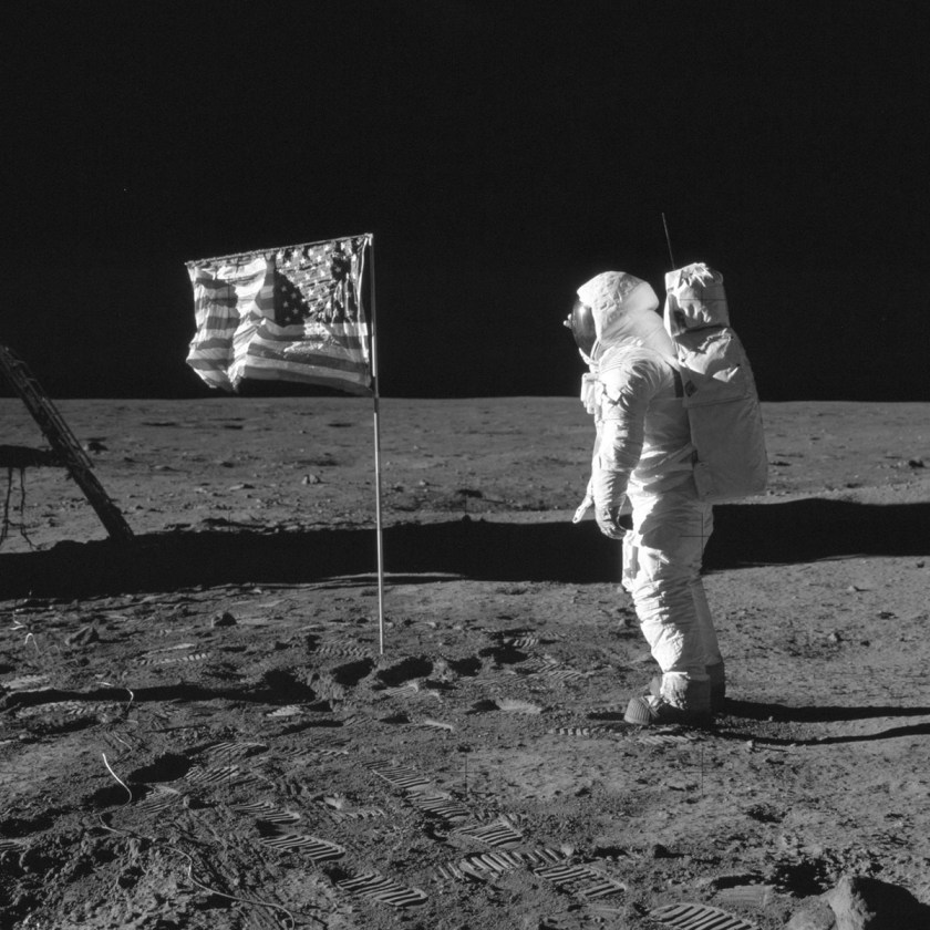 Iconic image of an astronaut in a space suit stands on the moon next to an American flag.