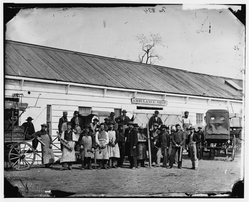 Men holding carpentry tools stand outside a building with wagons.