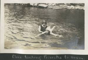 Photo of a young woman teaching another to swim.