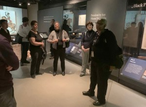 A group of people with a tour guide in a museum exhibition.